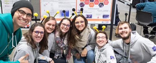 A group of students and a judge smiling in front of a poster at the 2019 Giant Jamboree