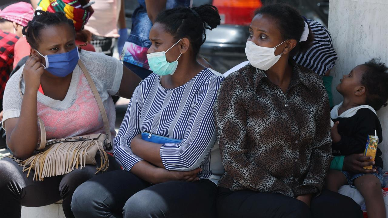 Ethiopian domestic workers wearing masks sit together with their belongings in front of the Ethiopian consulate in Hazmiyeh, Lebanon, June 8, 2020.
