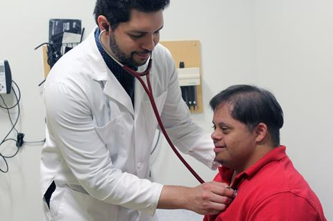Photo of young man with Down syndrome being treated by a doctor.