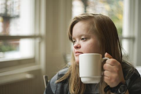 Image of a young woman with Down syndrome drinking from a mug and looking out a window.