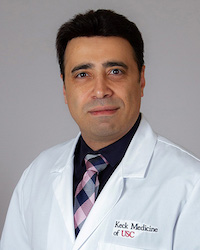 Pandemic expert Ali Gholamrezanezhad is photographed in his doctors attire in a portrait style photo. it says Keck Medicine of USC on his breast pocket of his uniform.