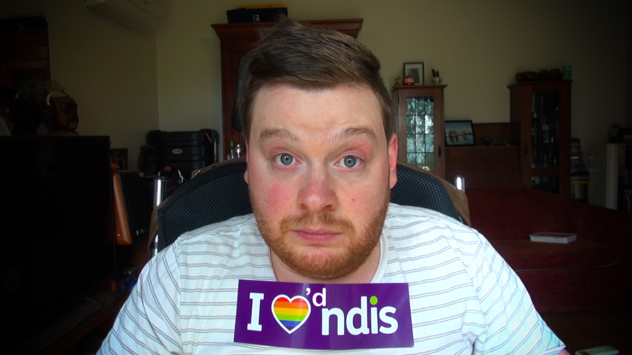"""Carl Thompson, a man using a wheelchair in his living room. He has a sticker on his chest that he has modified so that it reads """"I loved NDIS"""" instead of """"I love NDIS"""""""