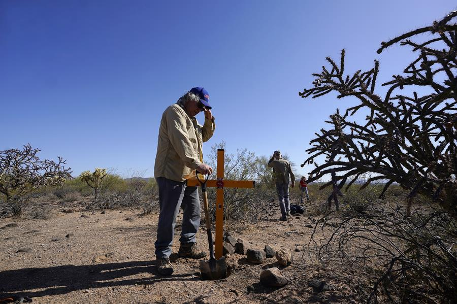 Alvaro Enciso, part of the Tucson Samaritans volunteer group, pauses as he and a group of other volunteers place a new cross at the site of the migrant who died in the desert some time ago, on Tuesday, May 18, 2021, in the desert near Three Points, Ariz.