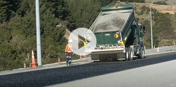 Chipseal being distributed from the back of a truck.