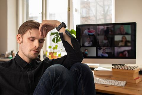 Man Fatigue during home video conference meeting call. Post-work exhaustion from constant face-to-face digital interactions