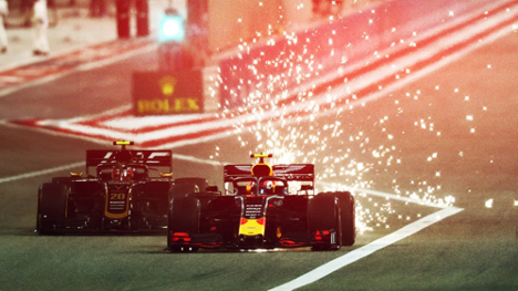 Formula One cars speeding down the track with sparks flying behind them